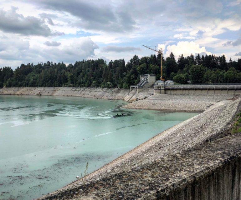 Im Norden des Forggensees bei Roßhaupten befindet sich der große Staudamm. Die Dammdichtung der Talsperre muss erneuert werden - daher herrscht hier aktuell Baubetrieb. © www.ichmachdannmalsport.de/Nina-Carissima Schönrock